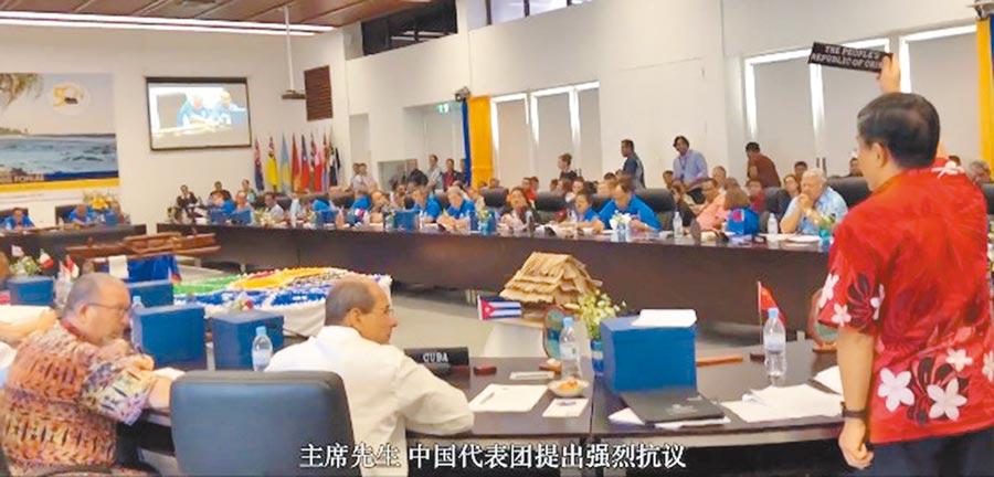 去年9月,擔任太平洋島國論壇特使的大陸外交官杜起文,因被阻撓發言,在會議上拿起桌牌起立抗議。(取自鳳凰新聞)
