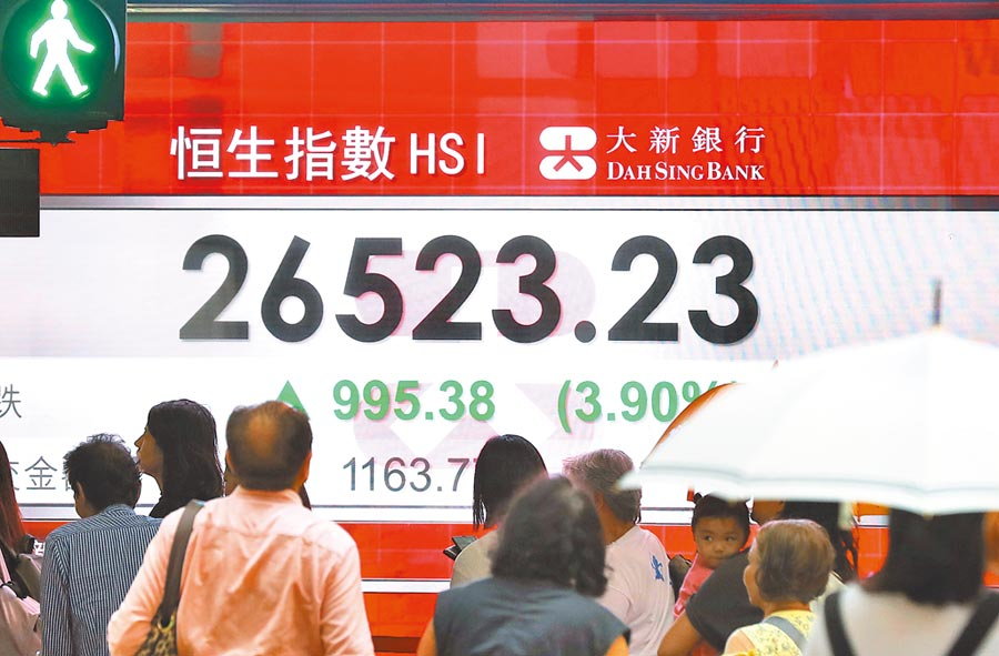 9月4日,香港恆生指數大漲995.38點。圖為民眾從香港中環的股市訊息螢幕前經過。  (新華社)