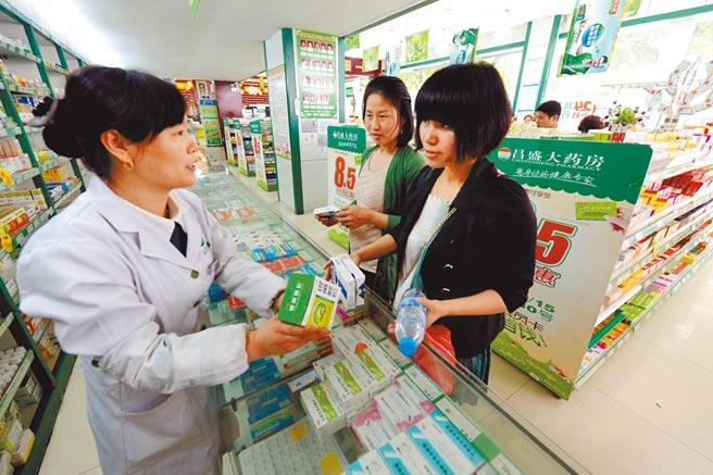 大陸可望開放網售處方藥。圖為某藥房執業藥師王志萍(左)向顧客介紹處方藥。(新華社資料照片)