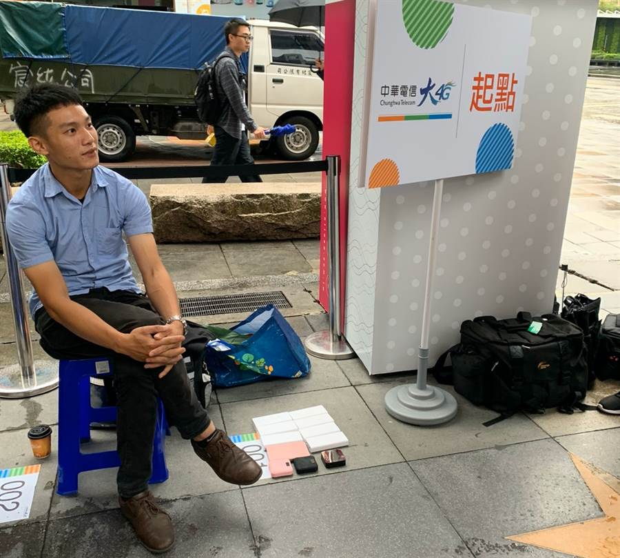 中華電信iPhone 11排隊頭香的洪先生跟他的11顆行動電源。(黃慧雯攝)