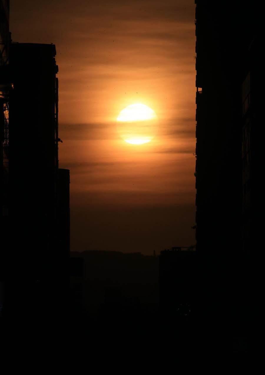 台中市掀起爭睹台中版「曼哈頓」懸日奇景,民眾在台中各處追逐散發金黃色光芒的「懸日」。(黃國峰攝)