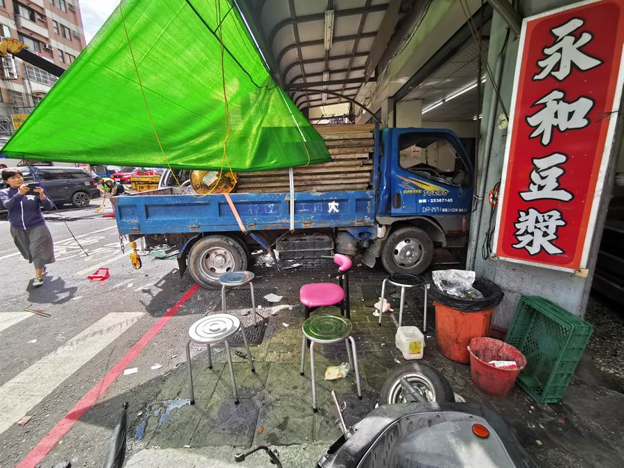 一輛載滿木建材棧板的小貨車,上午在莒光路、靜修路口與休旅車發生擦撞後直接撞進路旁一家早餐豆漿店,7名正在用餐的客人、路過行人慘遭波及。(吳建輝攝)