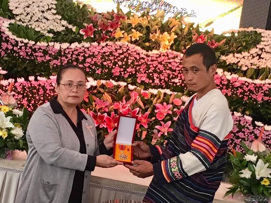 原民會副主委伊萬・納威(左)追頒柯菊蘭一等原住民族專業獎章,由其孫王伯元(右)代為受領。(原民會提供/廖德修傳真)
