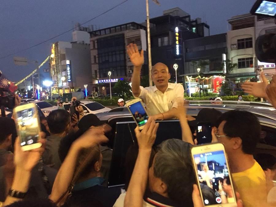 國民黨總統參選人韓國瑜(車上)21日晚間到東港參加「屏東藍軍大團結勝利餐會」,獲得大批韓粉擁戴,離開時忘情與大家揮手道別。(謝佳潾攝)