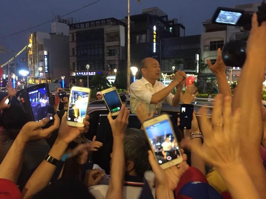 韓國瑜(車上)21日晚間到東港參加「屏東藍軍大團結勝利餐會」,獲得大批韓粉擁載,離開時忘情與大家揮手道別。(謝佳潾攝)