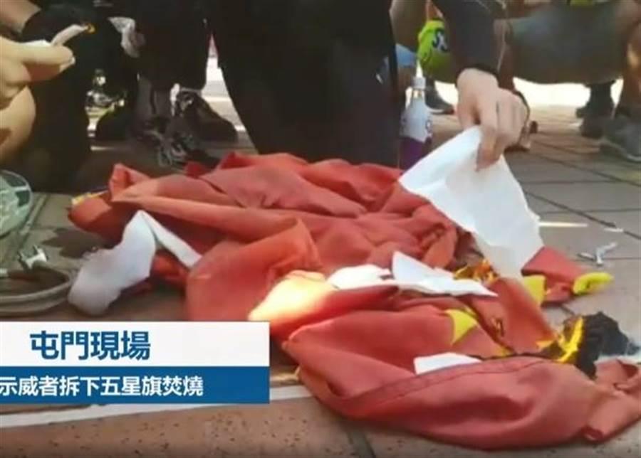 示威者拆下五星旗用打火機燒毀。(翻攝自東網)
