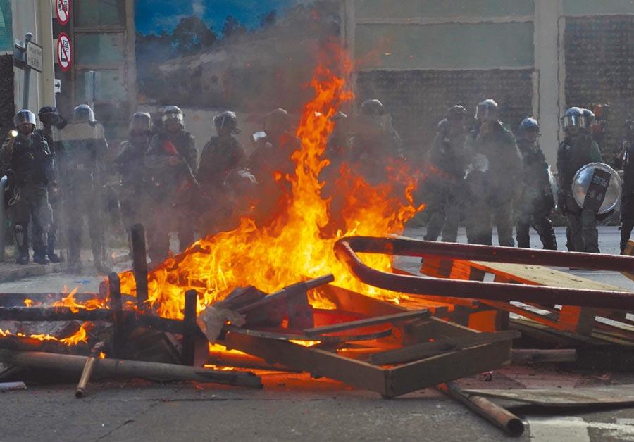 昨日的屯門遊行演變成暴力事件,有示威者搬來各種路障並當街縱火。(美聯社)