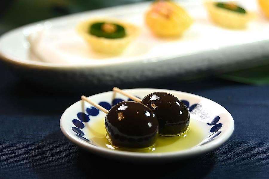 Constant張卓智設計的這Amuse Buche逗嘴小食,不是醃漬橄欖,而是被橄欖藻膠包覆的葡萄,吃時可搭配西班牙橄欖油。(圖/姚舜)