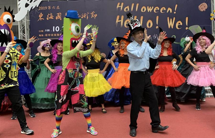 台中市經發局長張峯源(右)融入俏皮舞蹈,手持大型糖果邀請民眾參與商圈活動,氣氛熱鬧。(盧金足攝)