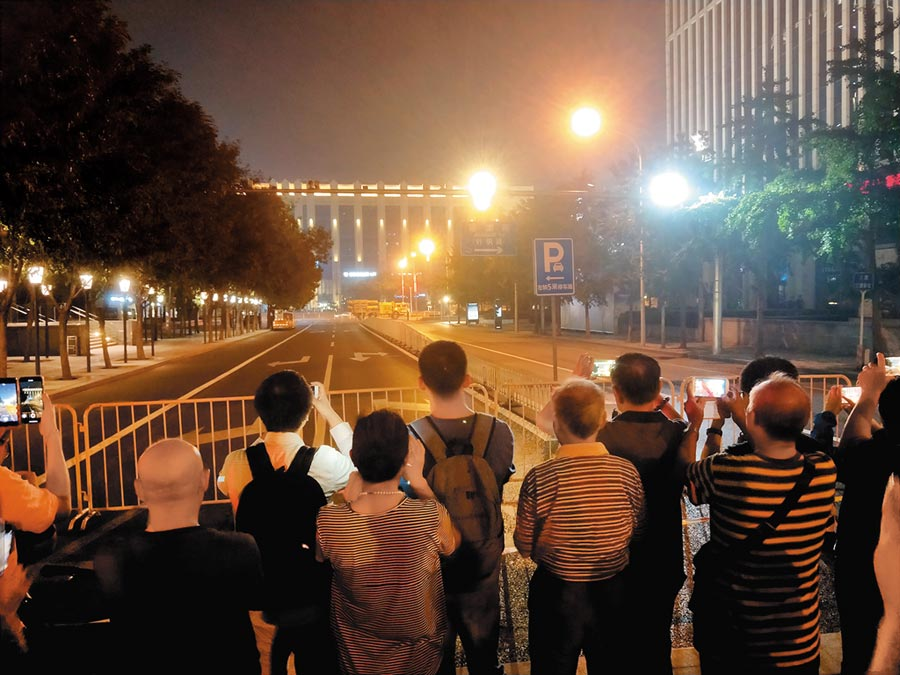 北京國慶彩排時,民眾聚在封鎖線前遠距離拍攝軍車通過。(記者陳君碩攝)