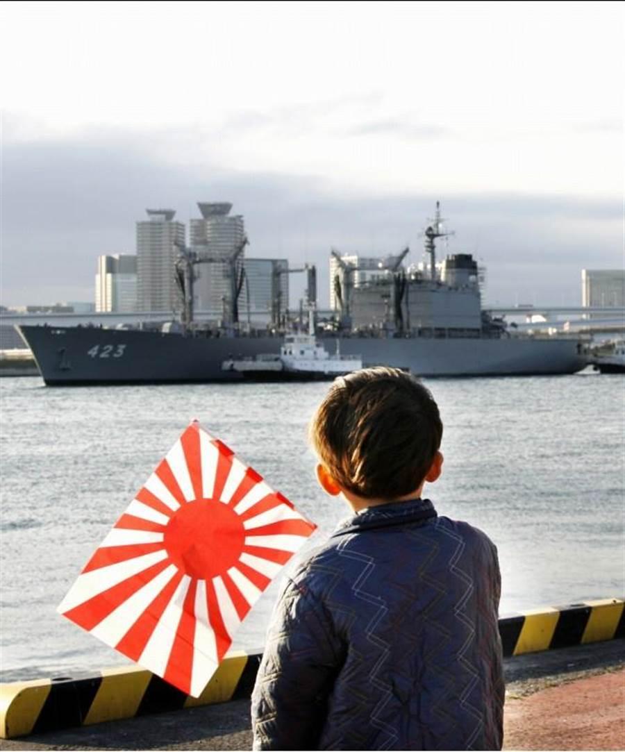 日本旭日旗是其軍國主義侵略亞洲的符號,是受害入民痛苦記憶中抹不掉的陰影。圖為2007年11月,日本海上自衛隊補給艦「常磐號」返回東京灣晴海碼頭時,一名小孩在岸邊揮舞著旭日旗。(美聯社)