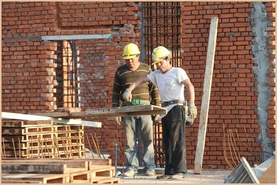 圖為建築工地的勞工忙碌工作。(資料照/陳怡誠攝)