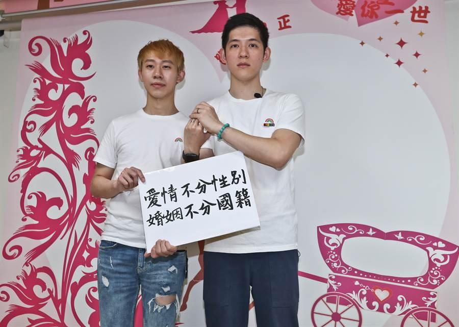手續結束後,信奇(左)與阿古(右)展示兩人的婚戒,並拿著「愛情不分性別,婚姻不分國籍」標語,為兩百多對的跨國同性伴侶爭取基本結婚權。(劉宗龍攝)