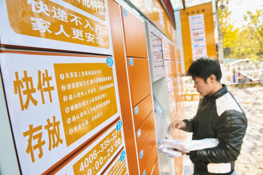 2014年11月17日,快遞員將快遞包裹投入安裝在秦皇島的智慧快件箱。(新華社)