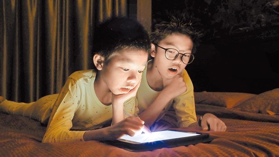 小朋友在夜間玩平板。(CFP)