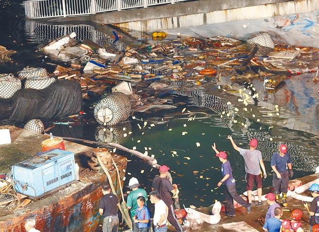 漁船遭斷橋壓毀並疑似還有多名外籍員工受困,船東在岸邊撒冥紙弔慰亡魂。(王英豪攝)