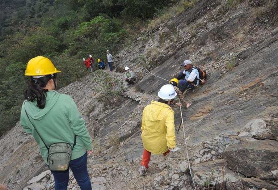 在通往舊大武的獵人古道上,手作步道志工們小心翼翼地踩著腳步,手拉著繩索或是扶著岩壁,驚險地通過大崩壁。(劉宗龍攝)v