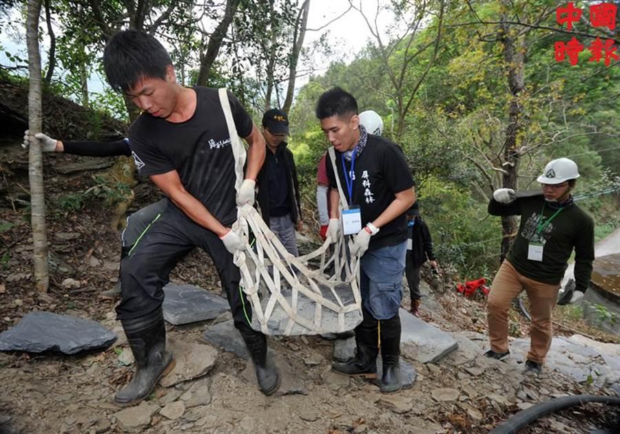 長期在部落蹲點的屏科大社區林業研究室學生林軒宇(左)及黃奎象(中),利用繩袋搬運石塊,為修築步道盡一份力。(劉宗龍攝)