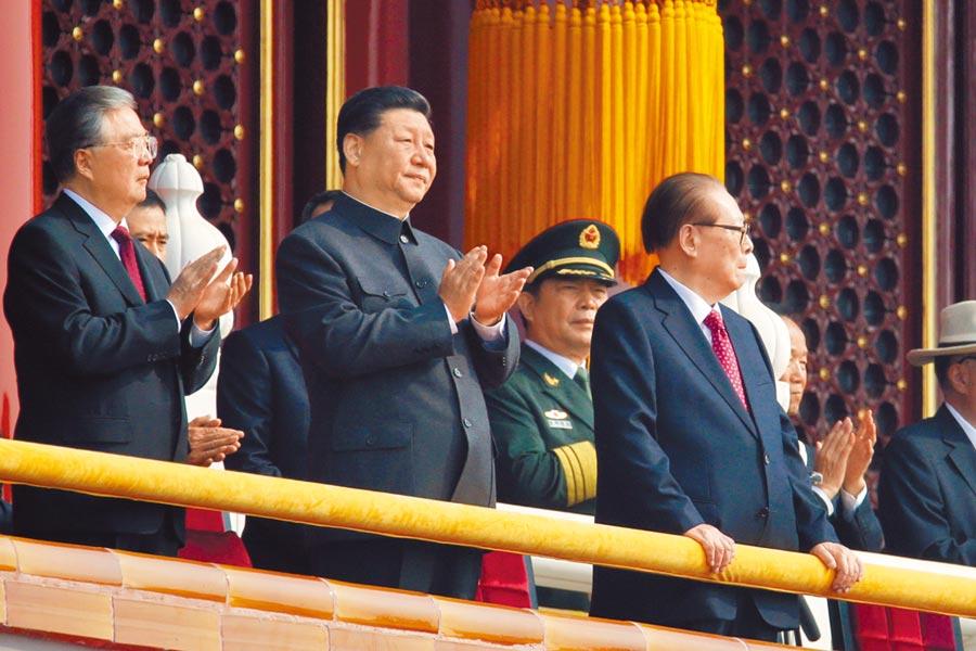 大陸國家主席習近平(中)與前領導人江澤民(右)、胡錦濤站在天安門城樓,觀看閱兵。(路透)
