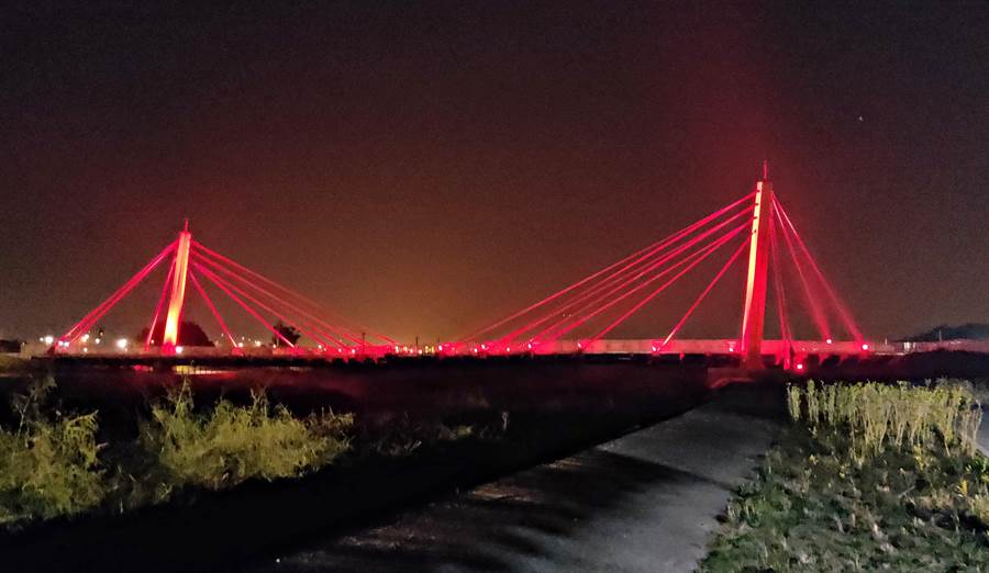 跨越西湖溪景觀橋以投射式地景照明設備妝點橋梁,讓河道增添浪漫氛圍。(苗栗縣政府提供/何冠嫻苗栗傳真)
