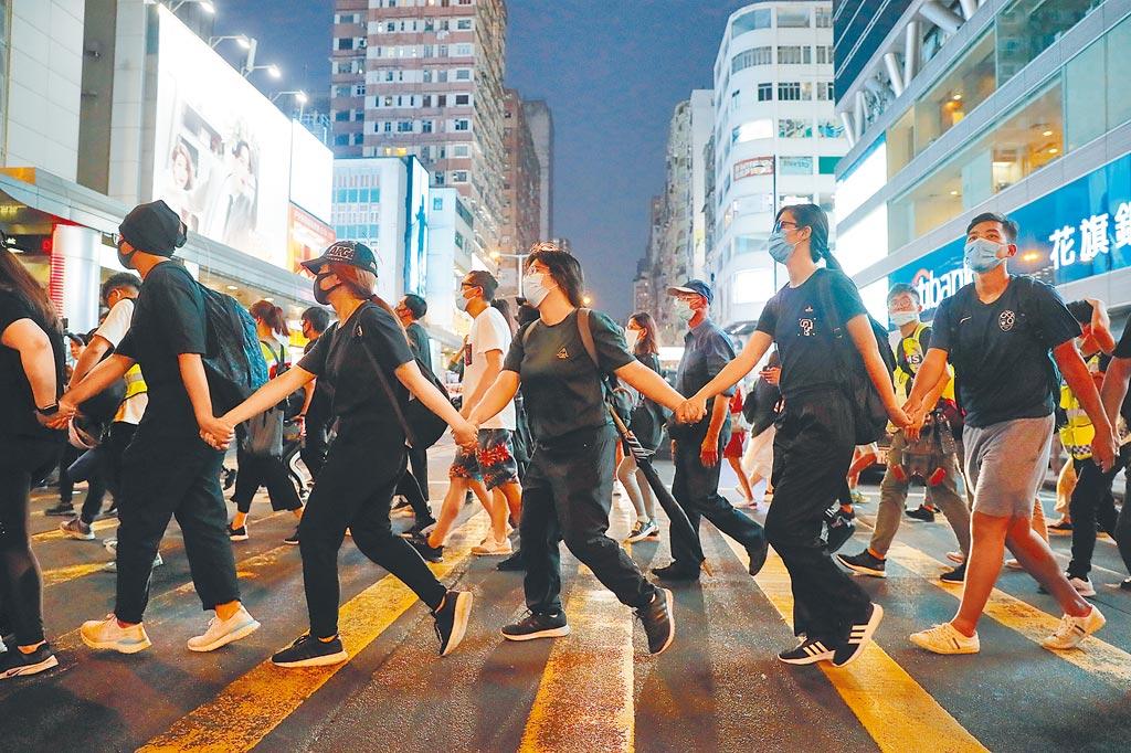 港府頒布《禁蒙面法》,仍有許多香港民眾5日晚間戴著口罩上街抗議,手牽手組成人鏈。(美聯社)