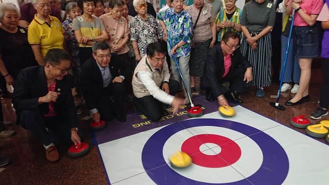 台南市長黃偉哲(米色背心)在安養院內與長輩玩冰壺遊戲。(程炳璋攝)