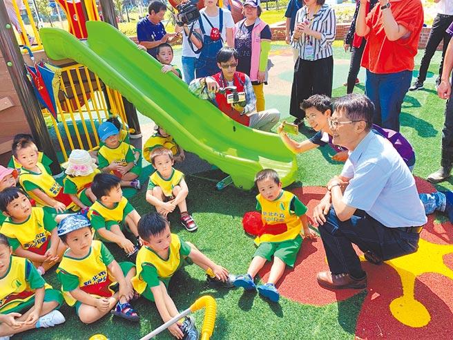 金山區杜鵑公園啟用,新北市副市長陳純敬蹲下身來,與幼兒園小朋友聊天、同樂。(張睿廷攝)