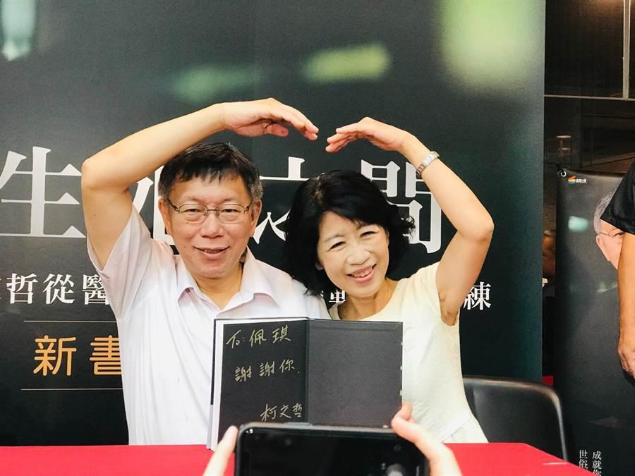 台北市長柯文哲(左)與妻子陳佩琪(右)6日下午在北車簽書會現場,高舉愛心手勢。(張穎齊攝)