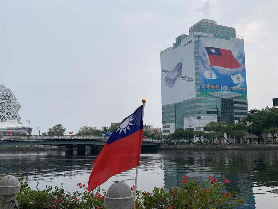 高市街頭出現國旗旗海飄揚景緻,其中以愛河為打卡熱點,有大一面建築外牆的國旗及橋上旗海。(柯宗緯攝)