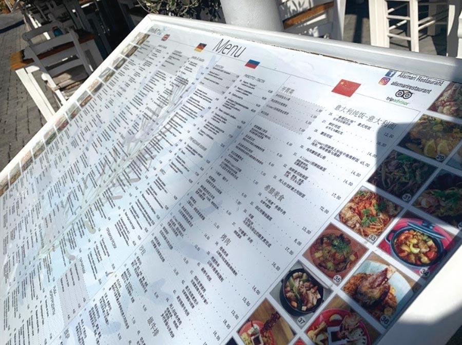 聖托里尼島卡瑪麗海灘旁的餐廳已提供英、法、德與中文的菜單,顯見中國遊客的勢力與歐洲遊客不相上下。圖╱林志昊