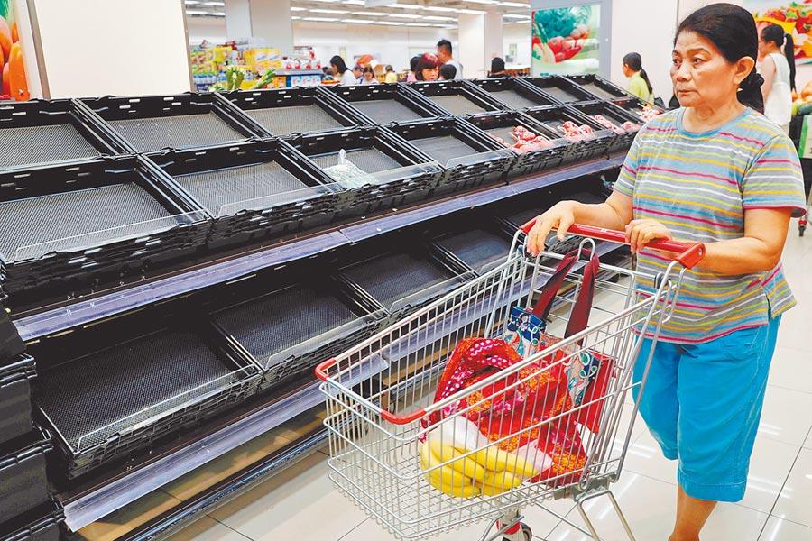 超市貨架商品空蕩蕩,幾乎被買光。(路透)