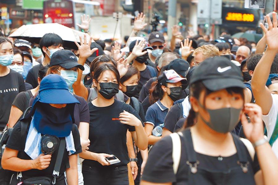 香港反送中示威者不理會港府祭出禁蒙面法,5日遊行時依舊戴上口罩。(中央社)