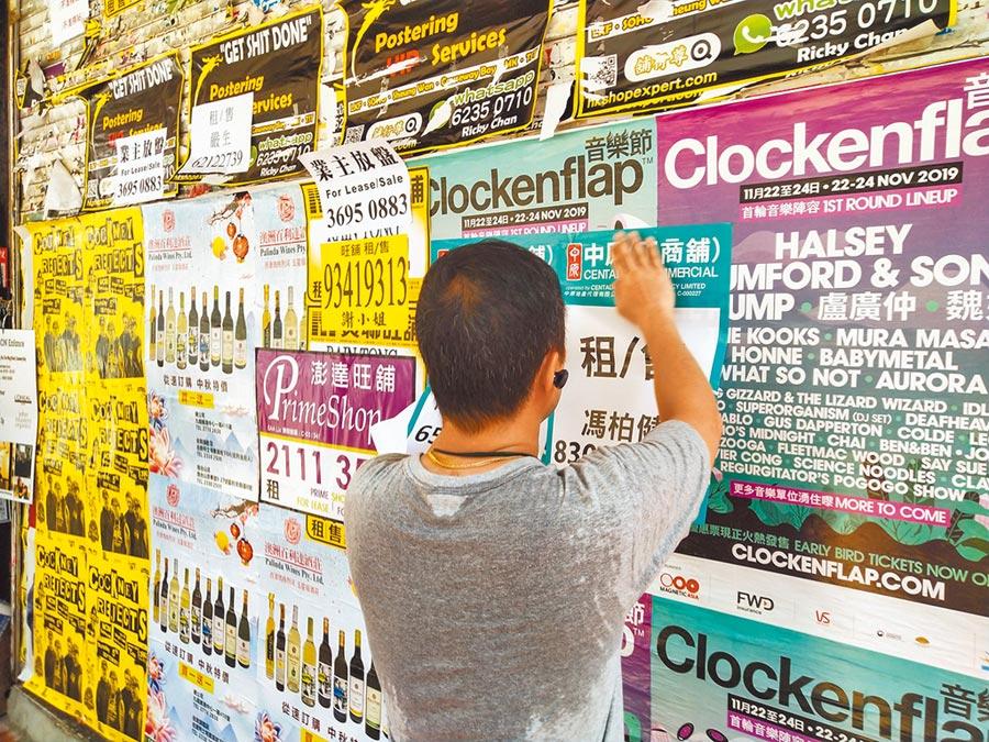 香港辦公大樓空置率上升至8.2%,圖為業者正在張貼商鋪租售訊息。(新華社)