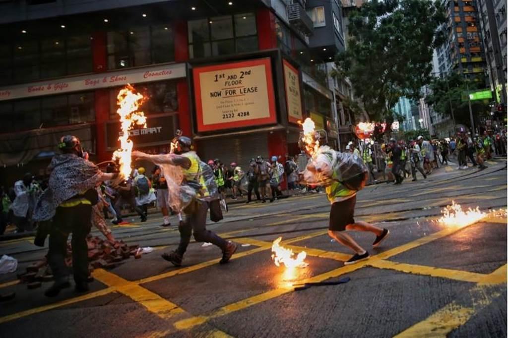 香港6日示威遊行中,有記者遭到示威者投擲的汽油彈擊中。(圖/美聯社)