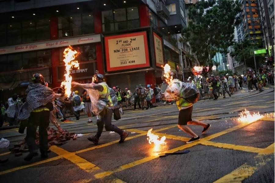 香港6日示威遊行中,有記者找遭到示威者投擲的汽油彈擊中。(圖/美聯社)