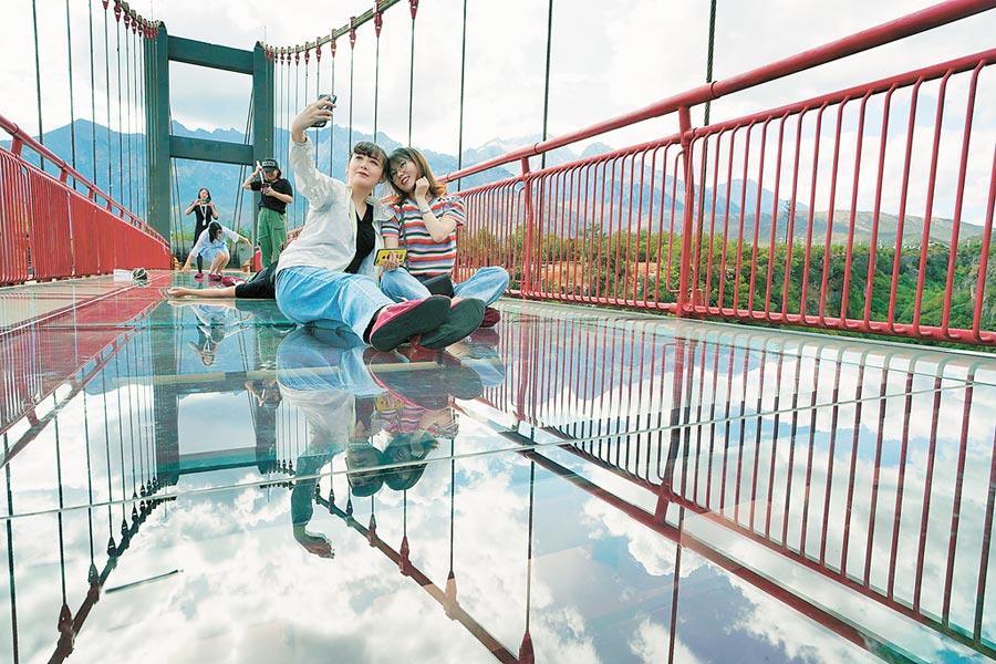 遊客在雲南省麗江市玉龍雪山山腳下的「東巴祕境玻璃棧道」上留影。(新華社)