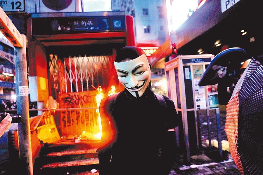港府開出《禁蒙面法》第一槍後,各界都在擔憂「禁網」可能隨之而來。圖為一名反送中示威者站在遭縱火的港鐵站前。(路透)