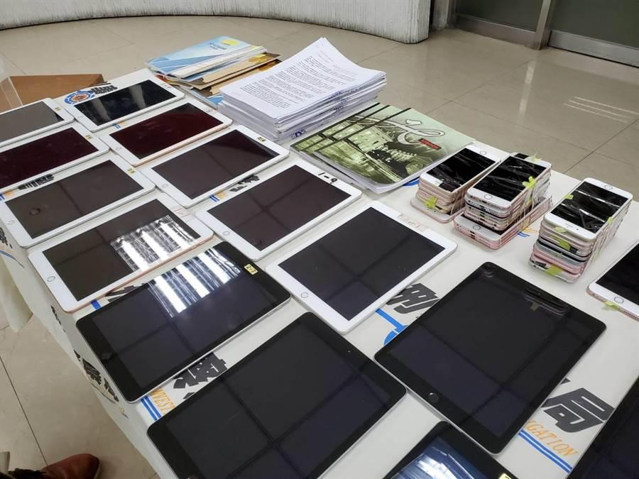 警方查獲平板電腦、手機、詐欺教戰手冊、筆記本等贓證物。(林郁平攝)