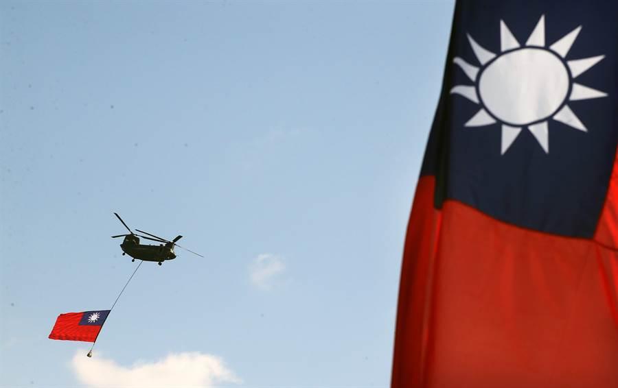 國軍CH-47D直升機,繫一面超大國旗,飛越台北市上空。(圖/范揚光攝)