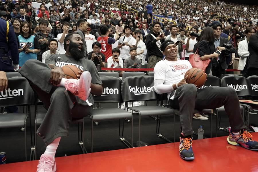 哈登(左)、韋斯布魯克賽前悠閒坐在板凳席上,看來並未受到莫瑞風暴影響心情。(美聯社)