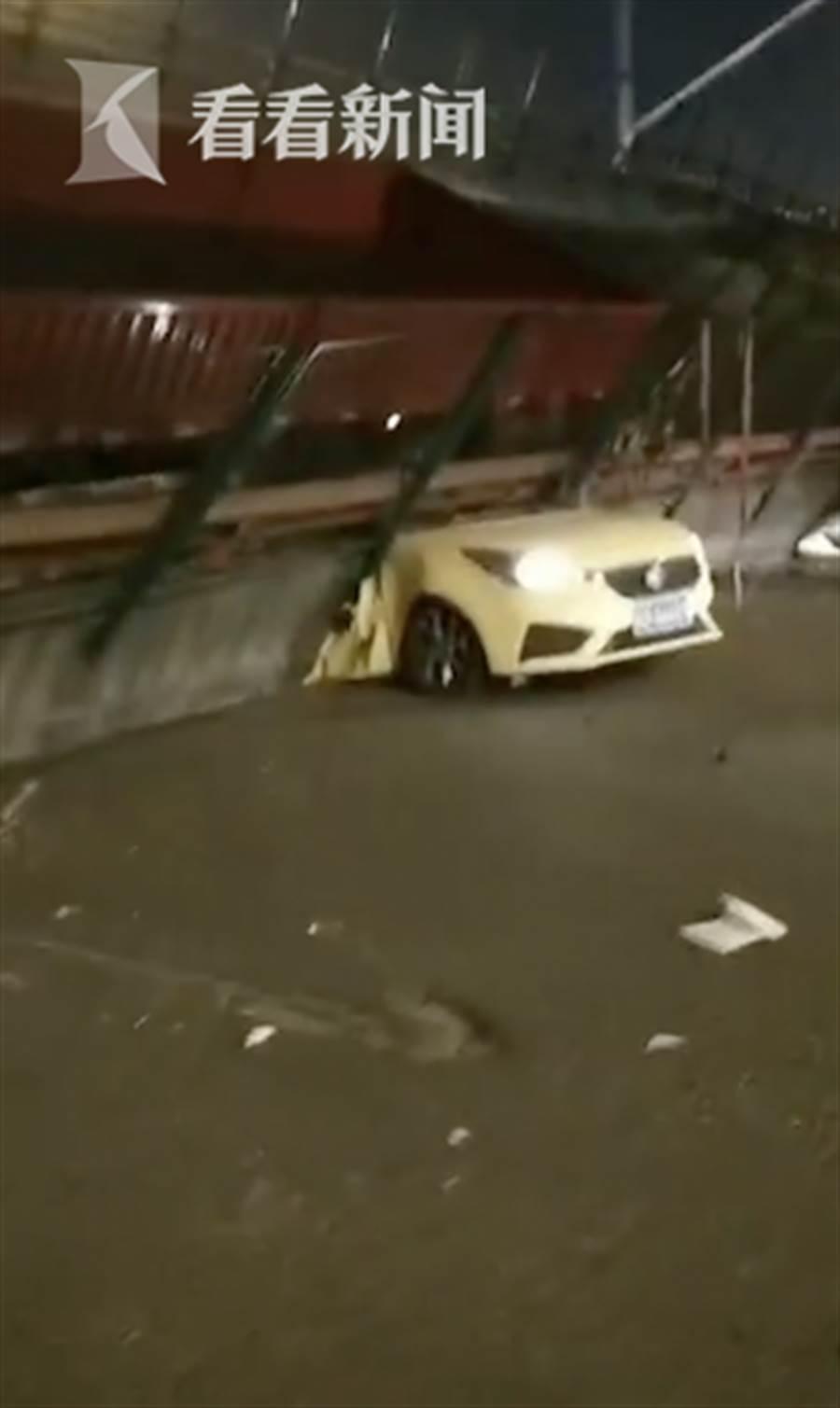 一輛行駛中的轎車被坍方的橋面壓住。(翻攝自看看新聞)