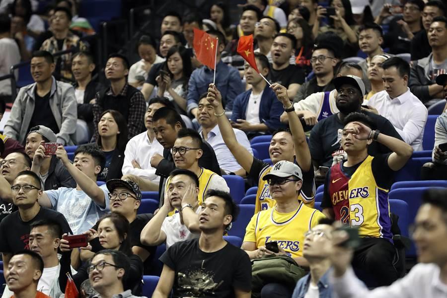 遭到央視與陸媒抵制的NBA中國賽今天在上海如期舉行,雖然賽前記者會取消,但這場湖人對籃網的球賽仍吸引了滿場的觀眾,有些大陸民眾觀賞球賽時還不忘帶面國旗以展現愛國心。(圖/路透)