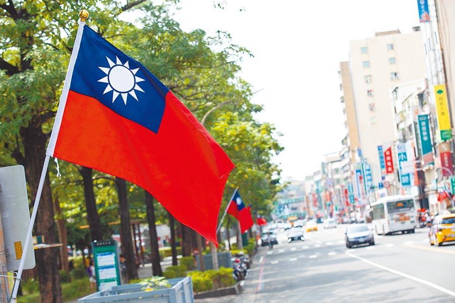 薛智能號召深綠友人共同出資3萬,在小港區漢民路懸掛國旗65面。(袁庭堯攝)