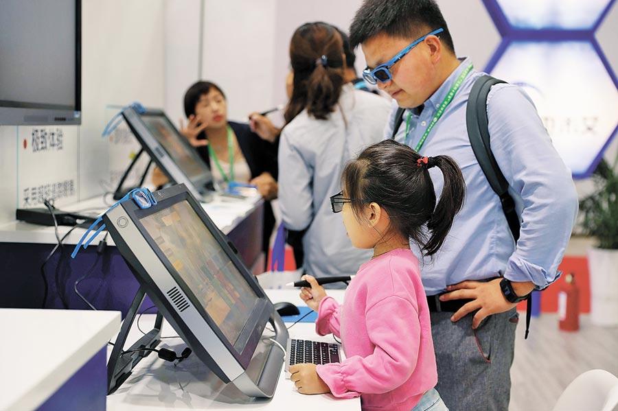 9月17日,首屆寧夏互聯網+教育博覽會,父親陪伴孩子體驗智慧教學平板。(中新社)