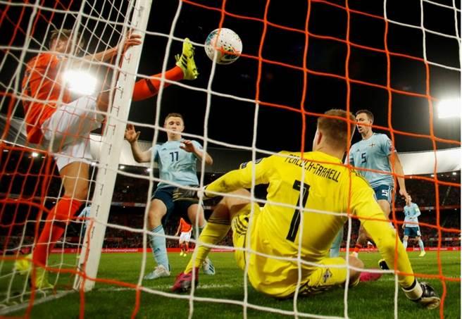 荷蘭替補中鋒路克德容(左)在門柱旁抬高右腿,踢進致勝球。(路透)