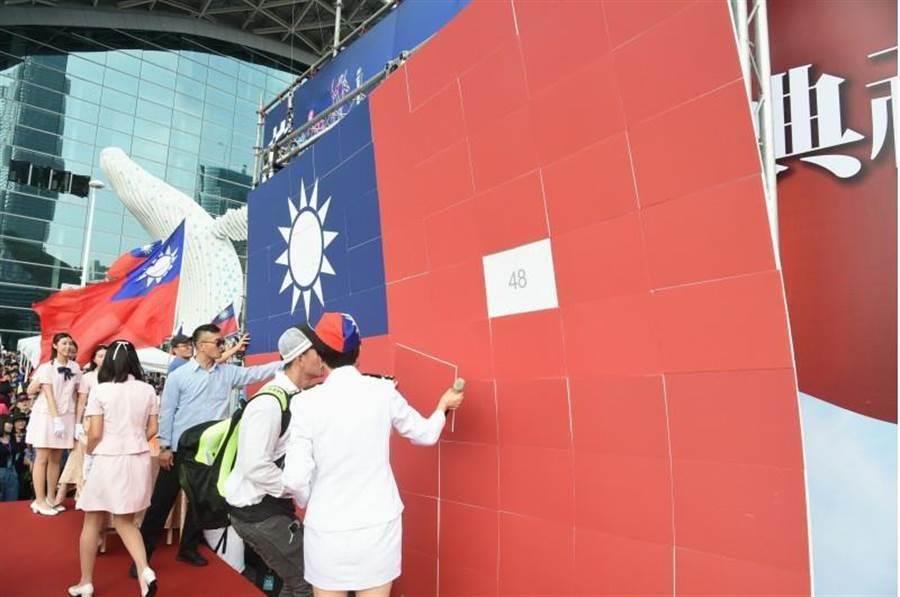 高雄市國慶升旗典禮,高雄市長韓國瑜致詞時,舞台後方拼製而成的巨幅國旗背板突掉落,背板露出2個數字「48」。(中央社)