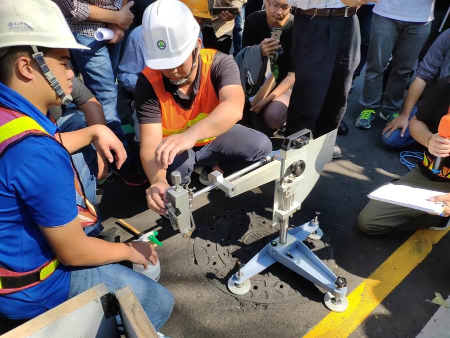 台中市建設局示範水性陶瓷水泥抗滑塗布,以及英式擺錘抗滑試驗方式,提升孔蓋抗滑性。(盧金足攝)
