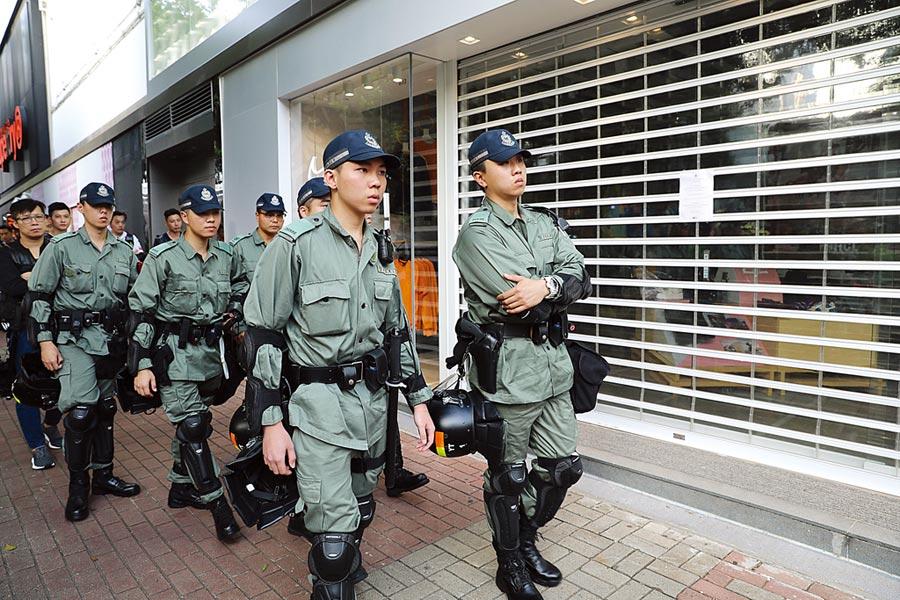 香港示威者在網上發起反送中集會,警員在商場外巡邏。大陸計畫對與反送中團體有關的美國籍人士,實施更嚴格的簽證限制。(中新社)