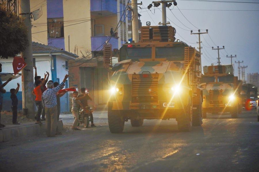 土耳其軍隊9日傍晚開赴敘利亞北部,在行經土國東南部邊境城鎮時,受到邊境民眾的歡呼。(美聯社)
