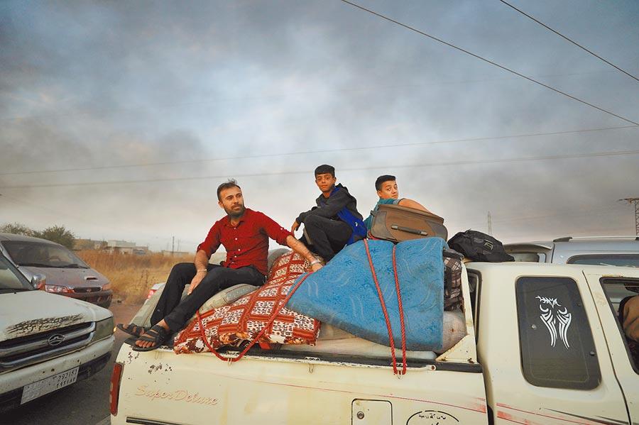 土耳其軍隊9日向敘利亞東北部城鎮艾因角發動密集炮擊和空襲,當地民眾開車載著家人及家當逃離。(路透)